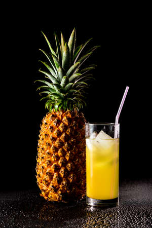 reflective: Pineapple with glass of juice on a black reflective background with drops of water, Studio shot,