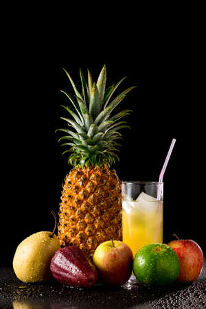 reflective: Composition with tropical fruits and  glass of juice on a black reflective background with drops of water, Studio shot,
