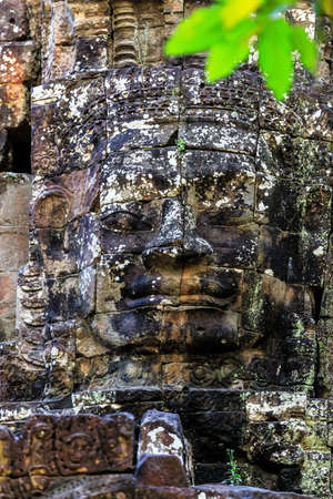 Giant stone faces of ancient buddhist khmer temple near Siem Reap, Cambodia Stock Photo