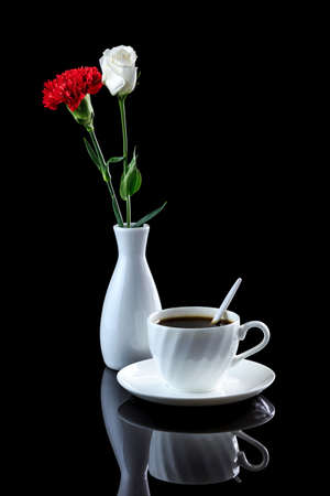 Composition with cup of coffee, white rose and red carnation on a black reflective background. Studio shot Stock Photo