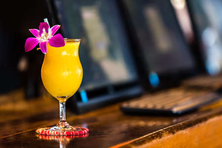 Yellow cocktail with orchid flower in the bar on the blurred background Stock Photo