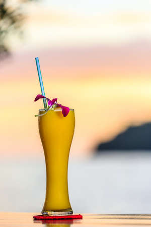 Yellow cocktail on the beach at sunset with blurred background. Vertical Stock Photo
