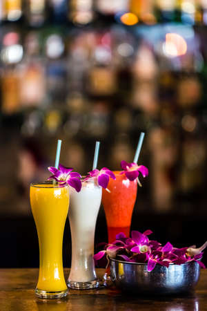 Vertical  composition with 3 yellow, white, red cocktails and orchid flowers on the blurred background