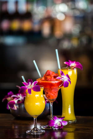 Composition with 3 yellow and red cocktails and orchid flowers on the blurred background. Focus on red cocktail