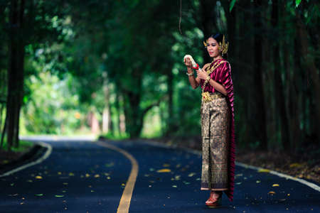 Beautiful Woman with Thai Traditional Dress King Rama posing in the tropical forest