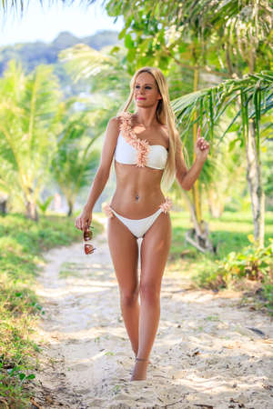 Beautiful woman in white bikini walking between palm trees at the tropical beach. Karon, Phuket, Thailand 写真素材