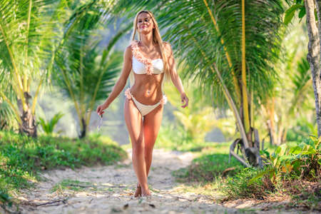Beautiful woman in white bikini walking between palm trees at the tropical beach. Karon, Phuket, Thailand Standard-Bild