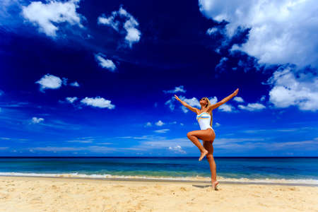 Happy girl in white swimsuit jumping at Karon beach, Phuket, Thailand Фото со стока