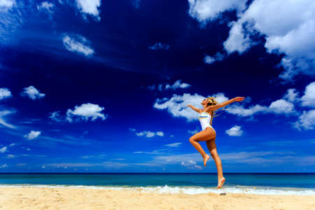 Happy girl in white swimsuit jumping at Karon beach, Phuket, Thailand Reklamní fotografie