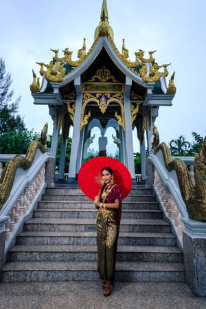 Beautiful Woman with Thai Traditional Dress King Rama posing near the temple
