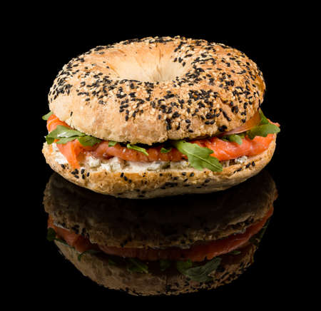 Smoked Salmon Bagel - Fresh baked bagel, cream cheese topped with smoked salmon and red onions with reflection isolated on black background
