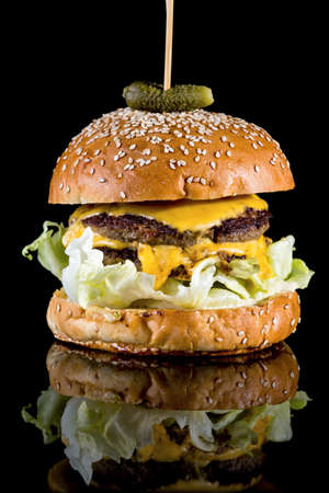 Cheese Burger - Large slab of matured cheddar and American cheese slice with reflection isolated on black background
