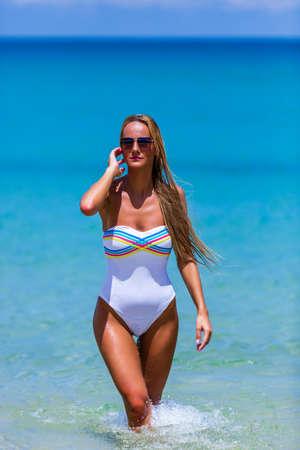 Sexy slim woman in white bikini walking through the water at Karon beach, Phuket, Thailand 写真素材