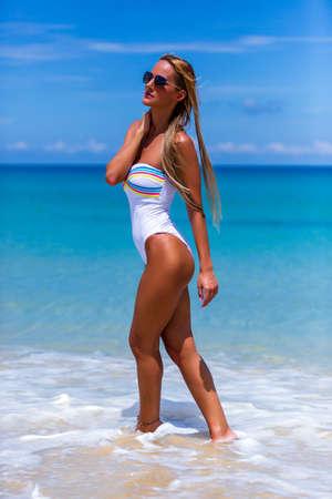 Sexy schlanke Frau im weißen Bikini zu Fuß durch das Wasser am Strand von Karon, Phuket, Thailand Standard-Bild