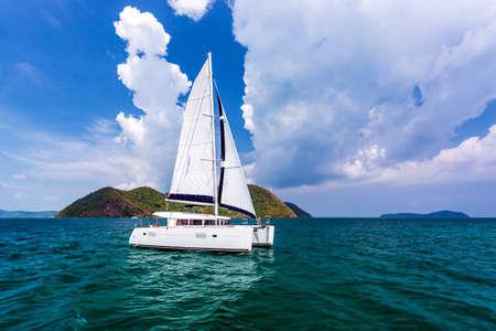 Catamarano bianco sulle increspature dell'acqua nel mare delle Andamane con cielo blu e nuvole a Phuket, Thailandia