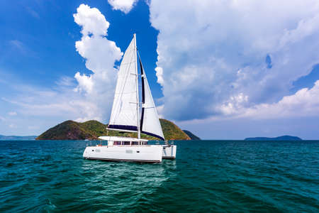 White catamaran on ripples the water in Andaman sea with blue sky and clouds at Phuket, Thailand