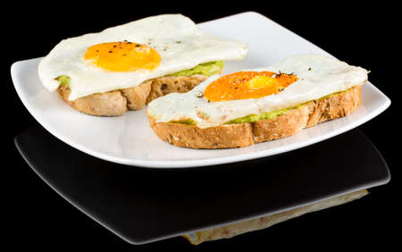 Avocado toasts topped with fried eggs with reflection isolated on black background. Studio Shot