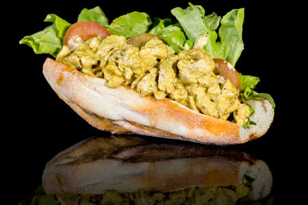 CHICKEN CURRY BAGUETTE with reflection isolated on black background. Studio Shot Stock Photo