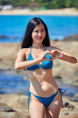 Schöne asiatische Frau, die Herz zeigt - Symbol der Liebe und Lächeln am Strand mit Felsen in einem blauen Bikini Standard-Bild