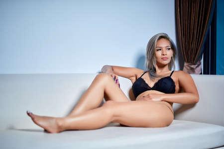 Sexy asian girl model in fancy black underwear lingerie is posing on the sofa