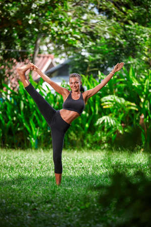Beautiful young woman practice yoga in the green tropical jungle