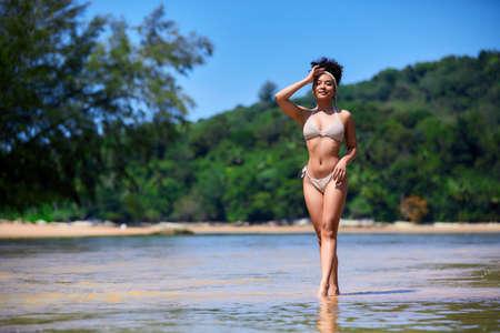 Young asian girl in bikini posing at Layan beach, Phuket, Thailand. Smiling Standard-Bild
