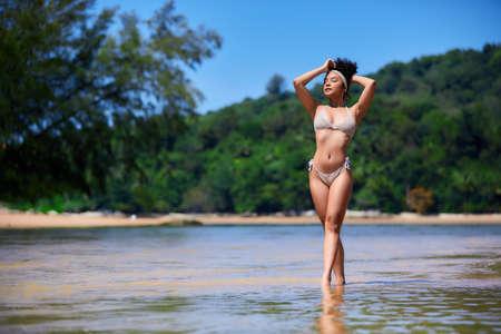 Young asian girl in bikini posing at Layan beach, Phuket, Thailand. Closed eyes