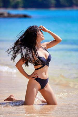 Beautiful asian woman enjoying on a tropical beach in a black swimsuit