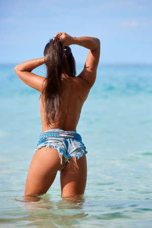 Sexy girl with long hair in the blue jeans shorts posing at the tropical beach in Thailand