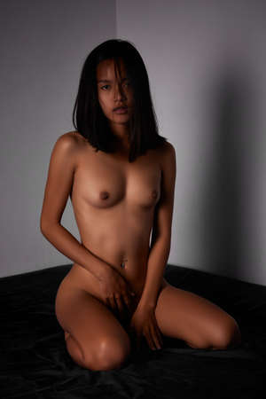 Naked asian girl sitting on the bed. Interior apartment bedroom Stockfoto