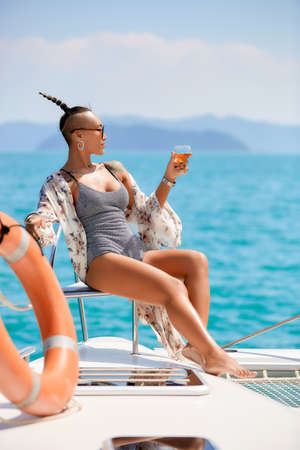 Fashion lifestyle portrait of young asian woman enjoying morning sun with glass of wine at white luxury yacht