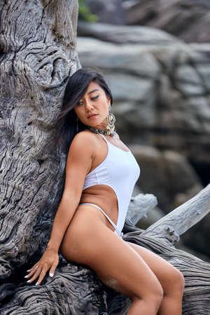 Beautiful hispanic woman posing on a tree in a white bikini
