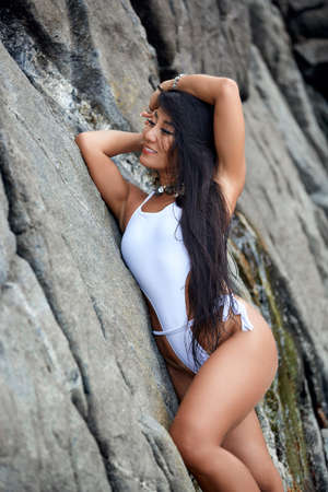 Beautiful hispanic woman posing on a beach with rocks in a white bikini Reklamní fotografie