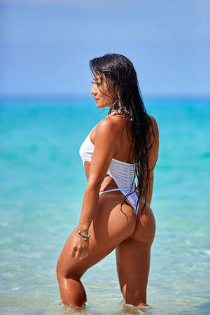 Sexy girl in white swimsuit posing at the tropical beach in Thailand