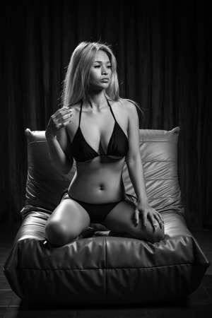 Sexy asian girl model in fancy black bikini is posing on the sofa