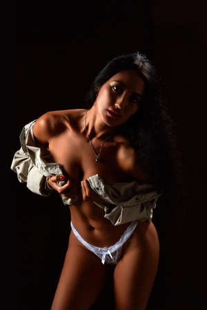 Art nude. Perfect body, young woman on the black background. Studio shoot