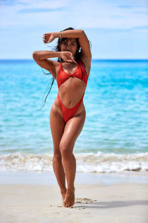 Sexy girl in red swimsuit enjoying on the sand at tropical beach in Thailand