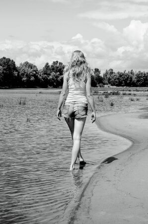 Beautiful slim tanned fitness girl s backwalking along the river. Blonde girl in jeans shorts. Banco de Imagens