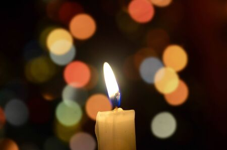 meditative: Burning candle light on abstract color bacground. Colorful bokeh Stock Photo