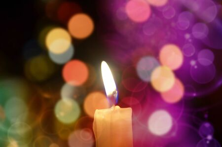 advent time: Burning candle light on abstract color bacground. Colorful bokeh Stock Photo