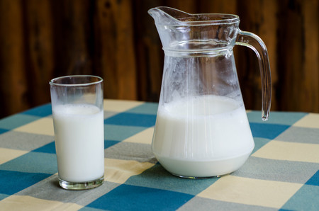 microelements: Pitcher and glass of milk checkered tablecloth in a farm