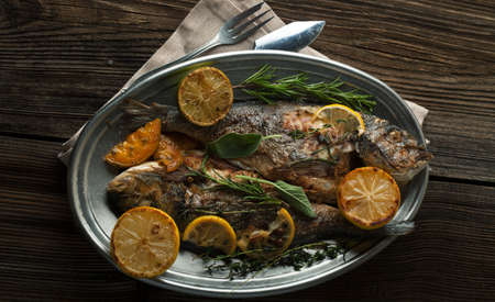 dorada: Grilled Dorada with a lemon and spices on a wooden background