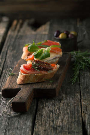 Bruschetta with smoked salmon, cheese, herbs and olives on a wooden background