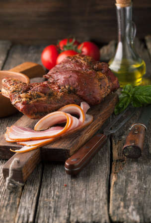 meaty: Delicious smoked bacon with spices, tomatoes and basil on a wooden background