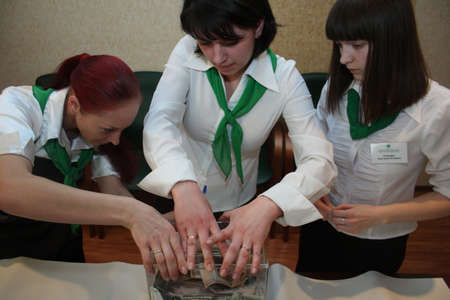 TOMSK, RUSSIA - APRIL 16: Employees of the Savings Bank counted the money - charity event to raise money for children suffering from cerebral palsy, April 16, 2009 in Tomsk, Russia.