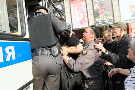 detain: MOSCOW - MAY 31: Police officers detain people during a banned anti-Kremlin protest in Moscow, May 31, 2010 in Moscow, Russia.