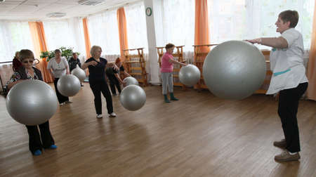 PODPOROZHYE, RUSSIA - JUNE 4: Day of Health in Center of\ social services for pensioners and the disabled Otrada (gymnastics\ with ball for elders), June 4, 2010 in Podporozhye, Russia.\