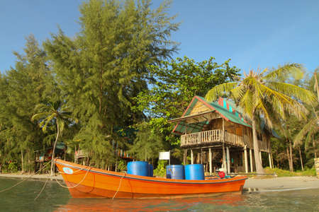 Boat and bungalow on the shores of the sea