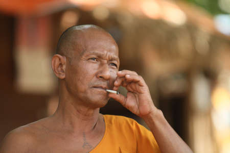 klong: KOH CHANG, THAILAND - DECEMBER 5: Smoking a cigarette unidentified monk in a Buddhist monastery Wat Klong Prao, December 5, 2011 in Koh Chang, Thailand.