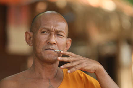 ordinate: KOH CHANG, THAILAND - DECEMBER 5: Smoking a cigarette unidentified monk in a Buddhist monastery Wat Klong Prao, December 5, 2011 in Koh Chang, Thailand.